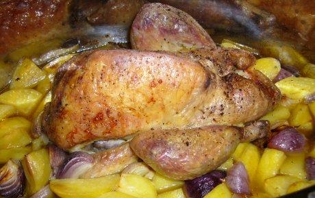 Gebratenes Perlhuhn mit Kartoffeln und Zwiebeln